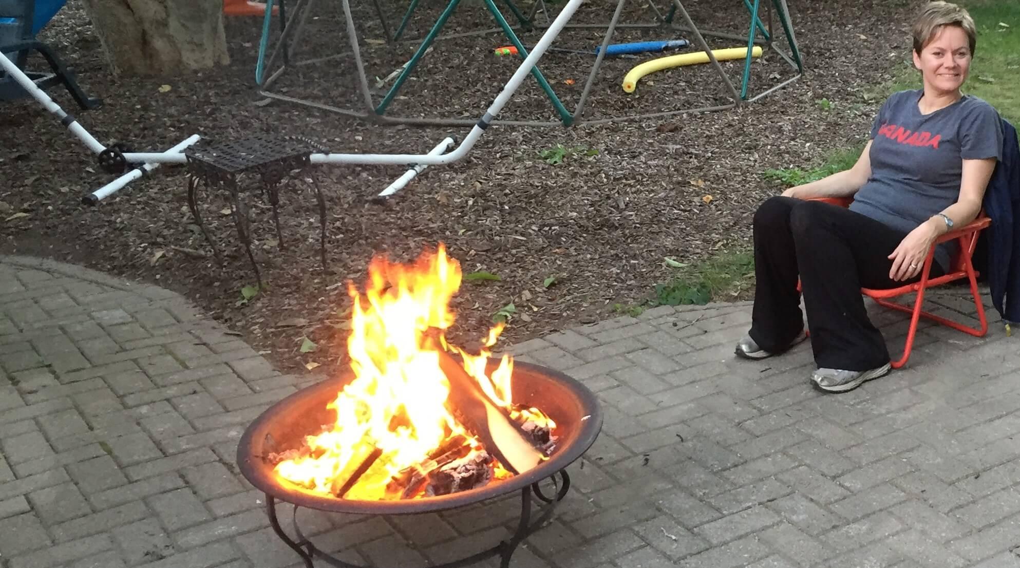 hannah-brown-sitting-by-backyard-campfire